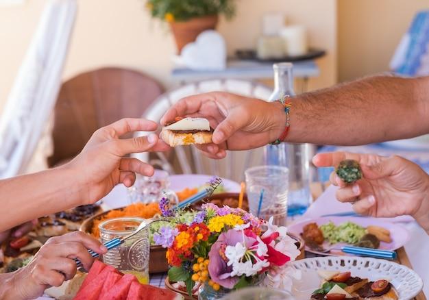 Gruppo di mani che condividono cibo e bevande popoli caucasici che si godono il brunch insieme