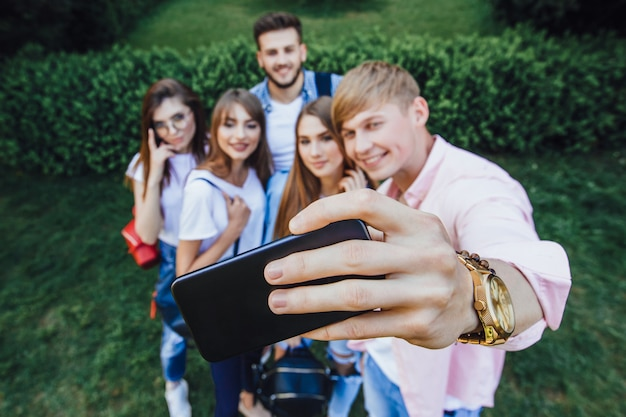Un gruppo di bei giovani che si fanno un selfie in un campus.