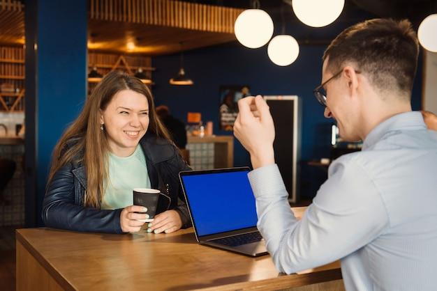 Gruppo di uomini d'affari felici che hanno discussione in ufficio davanti a una tazza di caffè
