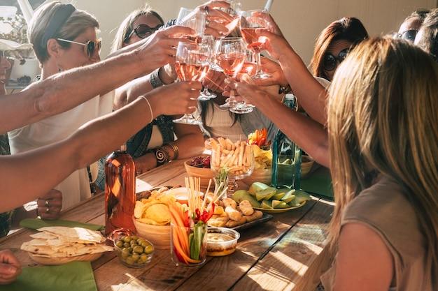 Un gruppo di persone allegre e allegre si diverte tutti insieme a bere e brindare con vino rosso red