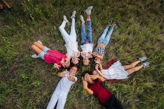 Un gruppo di bambini felici è sdraiato sull'erba a forma di cerchio e sorride felice.