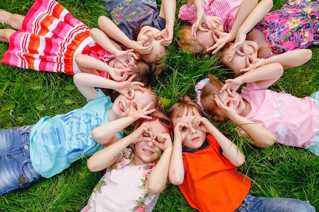 Un gruppo di bambini felici ragazzi e ragazze sdraiati nel parco sull'erba in una soleggiata giornata estiva.