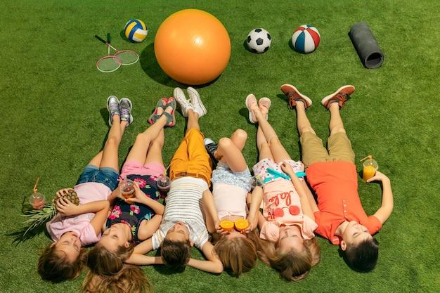 Gruppo di bambini felici che giocano all'aperto. bambini che si divertono nel parco di primavera. amici sdraiati sull'erba verde. ritratto vista dall'alto