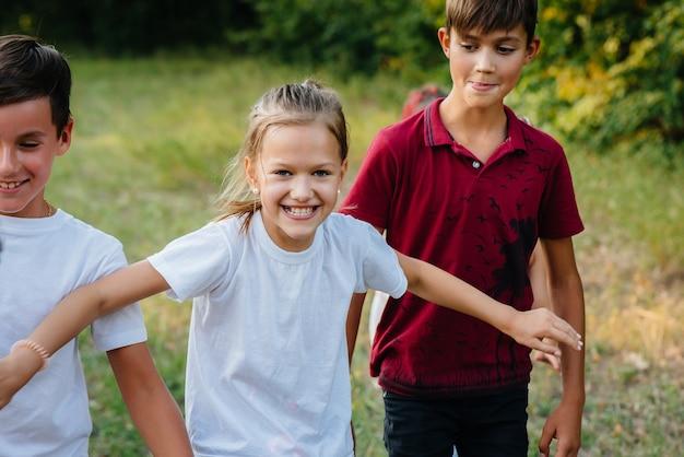 Un gruppo di bambini felici corre e gioca nel parco durante il tramonto. campo estivo per bambini.