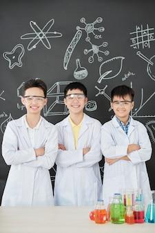 Gruppo di studenti asiatici fiduciosi felici in occhiali e camici in piedi al tavolo con bicchieri pieni di reagenti colorati