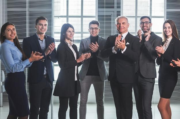 Gruppo di dipendenti aziendali felici che applaudono il loro successo