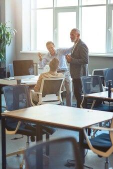 Gruppo di colleghi felici che parlano discutendo qualcosa e sorridono mentre lavorano insieme in