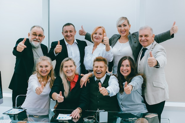 Gruppo di dipendenti felici che mostrano i pollici in su. concetto di successo