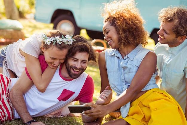 Gruppo di amici felici utilizzando il telefono cellulare