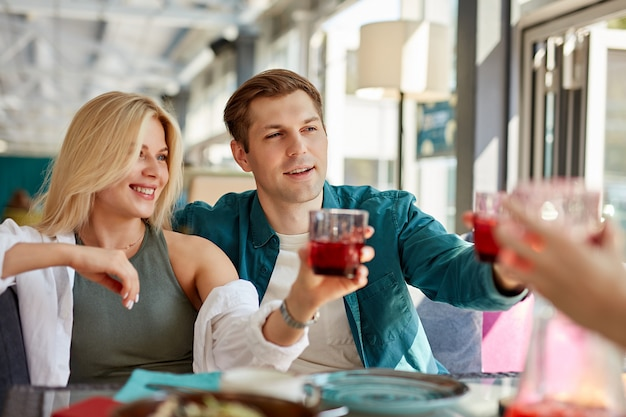 Gruppo di amici felici che celebrano nella caffetteria