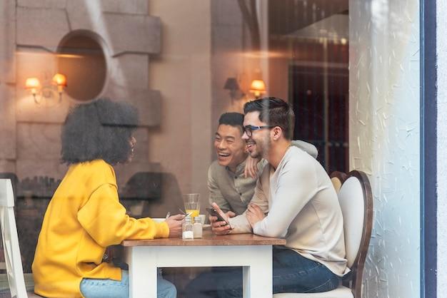 Gruppo di amici felici che chiacchierano nella caffetteria. concetto di amicizia.