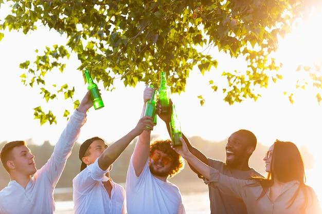 Gruppo di amici felici che tintinnano le bottiglie di birra durante il picnic in spiaggia sotto il sole. stile di vita, amicizia, divertimento, fine settimana e concetto di riposo. sembra allegro, felice, festeggiante, festoso.