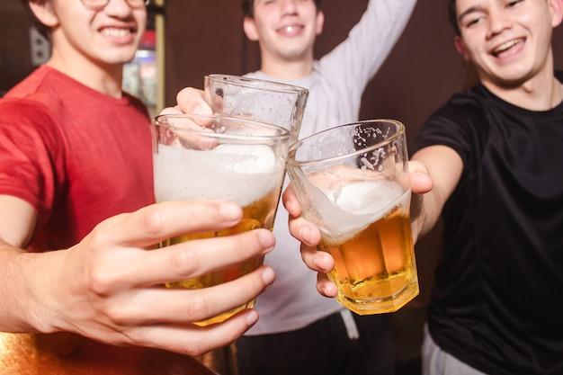 Un gruppo di amici felici che tintinnano i bicchieri con la birra.