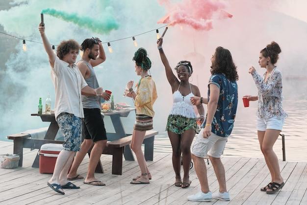 Gruppo di amici felici che ballano insieme su un molo tra fumo colorato