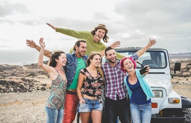 Gruppo di amici felici che fanno un'escursione sul deserto in auto 4x4 convertibile - giovani che si divertono a viaggiare insieme - amicizia, tour, gioventù, stile di vita e concetto di vacanza - focus sui volti di ragazzi