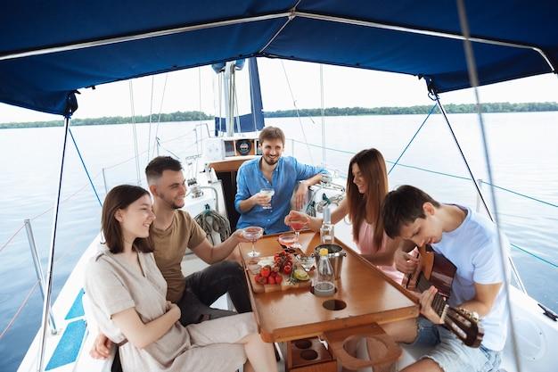 Gruppo di amici felici che bevono cocktail di vodka alla festa in barca all'aperto, estate