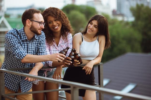 Gruppo di amici felici che fanno festa della birra in una giornata estiva