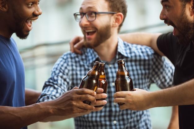 Gruppo di amici felici che hanno festa della birra in giornata estiva.