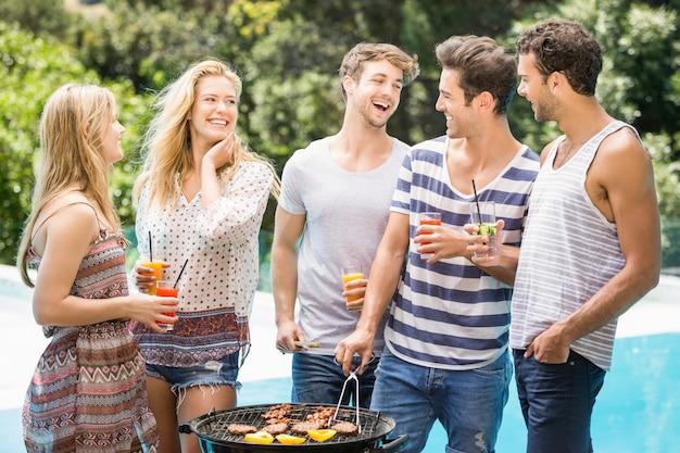 Gruppo di amici felici che preparano barbecue vicino allo stagno