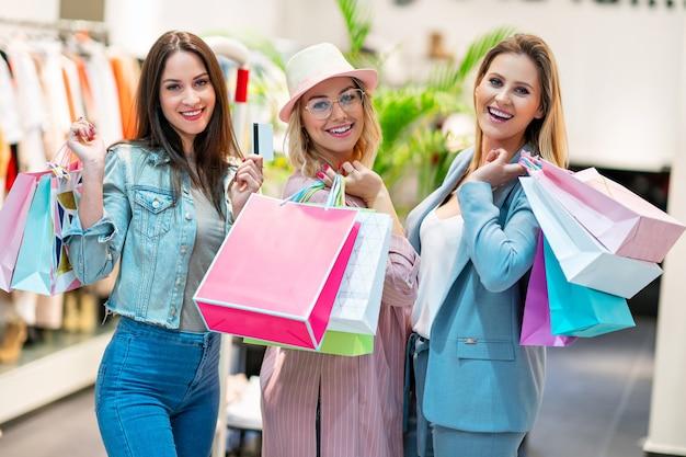 Gruppo di amici felici che acquistano vestiti nel centro commerciale