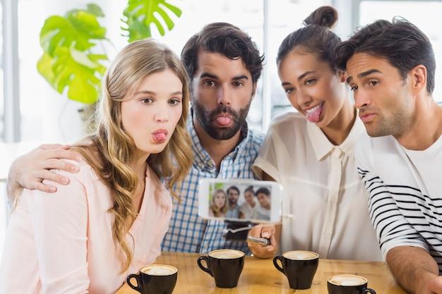 Gruppo di amici felici che prendono immagine con il bastone di slefie