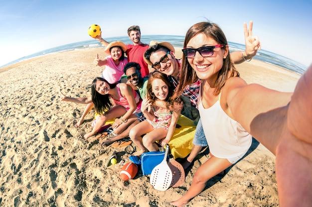 Gruppo di amici felici che prendono selfie e si divertono con i giochi di sport da spiaggia