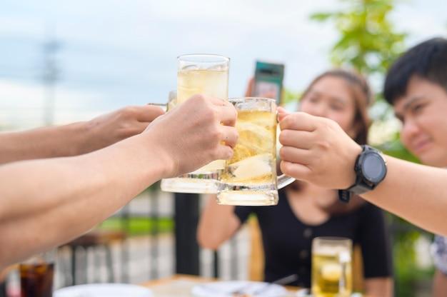 Gruppo di amici felici che tostano con un bicchiere di birra, concetto di amicizia.