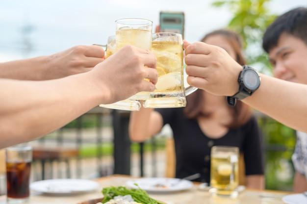 Gruppo di amici felici che tostano con un bicchiere di birra