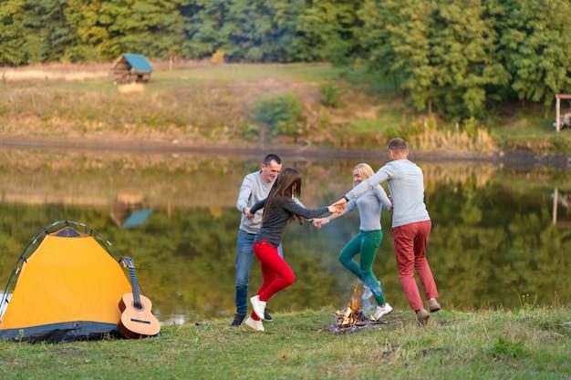 Gruppo di amici felici con la chitarra, divertirsi all'aperto, ballare e saltare vicino al lago nel parco