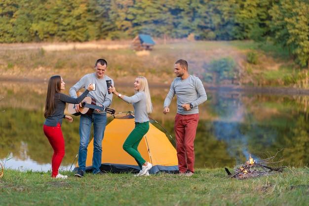 Gruppo di amici felici con la chitarra, divertirsi all'aperto, ballare e saltare vicino al lago nel parco Foto Premium