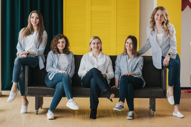 Gruppo di ragazze felici in posa sul divano. foto in studio.