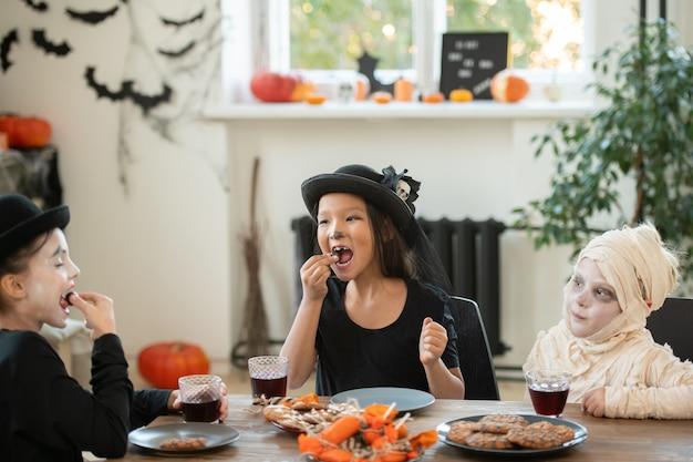 Gruppo di bambini felici in costumi di halloween seduti a tavola in un soggiorno decorato e mangiando biscotti e caramelle al tea party