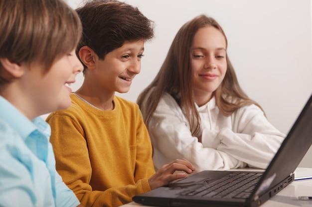 Gruppo di bambini felici divertendosi studiando insieme alla scuola di computer