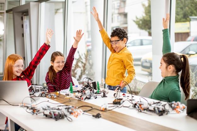 Gruppo di bambini felici che programmano giocattoli elettrici e robot in aula di robotica
