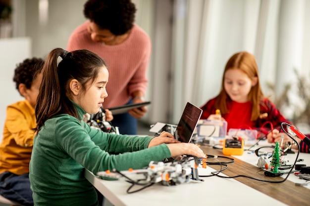Gruppo di bambini felici con il loro insegnante di scienze femminile afroamericano con laptop che programmano giocattoli elettrici e robot in aula di robotica