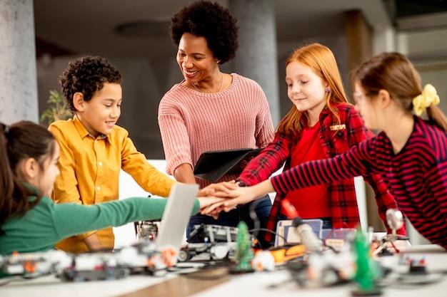 Gruppo di bambini felici con il loro insegnante di scienze femminile afroamericano