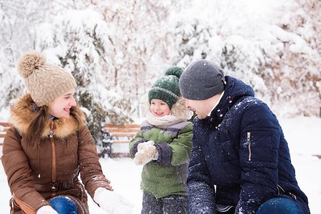 Gruppo di uomini e donne felici che si divertono e giocano con la neve nella foresta invernale