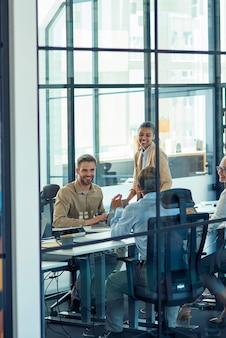 Gruppo di uomini d'affari multirazziali felici seduti nella sala riunioni dell'ufficio moderno e