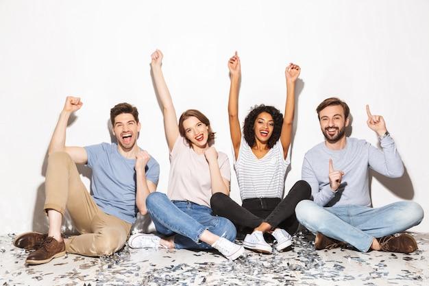 Gruppo di gente multirazziale felice che si siede su un pavimento
