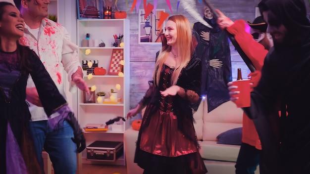 Gruppo di persone felici che si divertono e ballano alla festa di halloween mascherate da diversi personaggi spaventosi