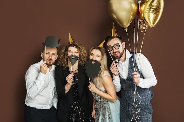Un gruppo di persone felici che indossano cappelli da festa con divertenti oggetti di scena per cabine fotografiche stanno celebrando una vacanza o un evento