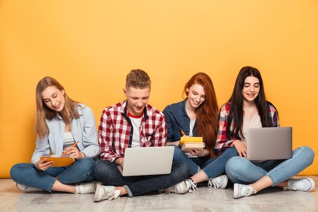 Gruppo di amici di scuola felici che fanno i compiti