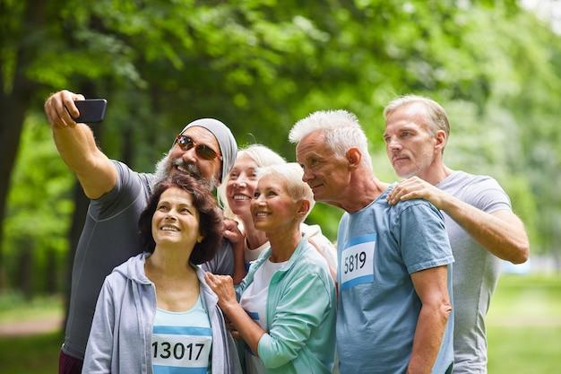 Gruppo di amici senior felici che prendono parte alla gara di maratona estiva in piedi insieme nel parco forestale prendendo foto di gruppo selfie