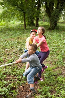 Gruppo di bambini sorridenti felici che giocano al tiro alla fune con la corda in parco verde,