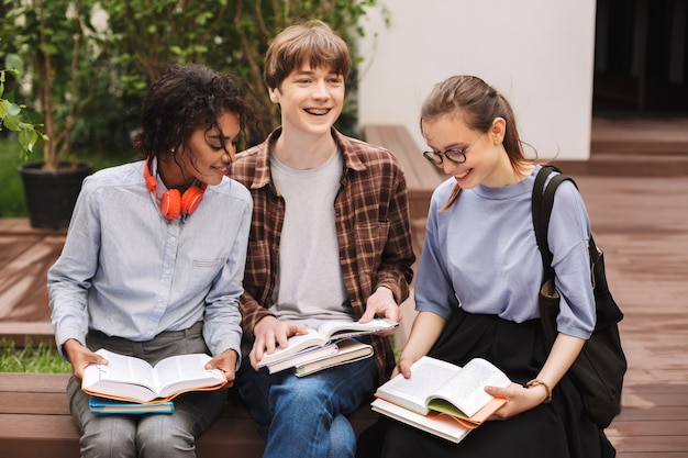 Gruppo di studenti felici seduti sulla panchina e leggere libri nel cortile dell'università
