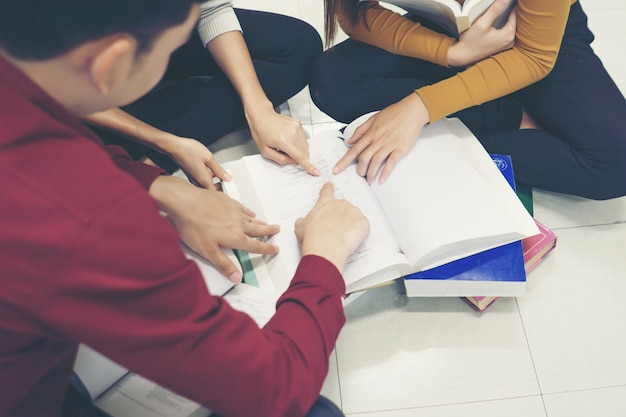 Gruppo di studenti felici con libri che parlano e preparano per esame in biblioteca. concetto di educazione.