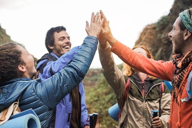 Gruppo di escursionisti felici che si accatastano le mani all'aperto