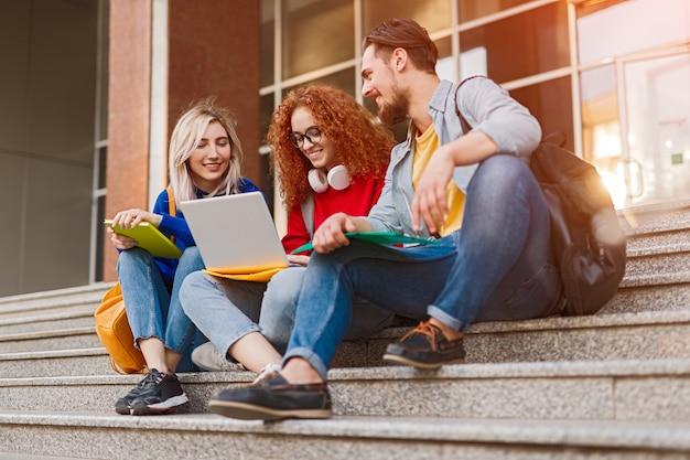 Gruppo di studenti universitari felici seduti sulle scale