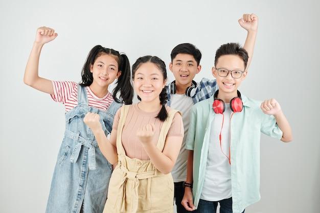 Gruppo di scolari vietnamiti felici alzando le mani e sorridendo