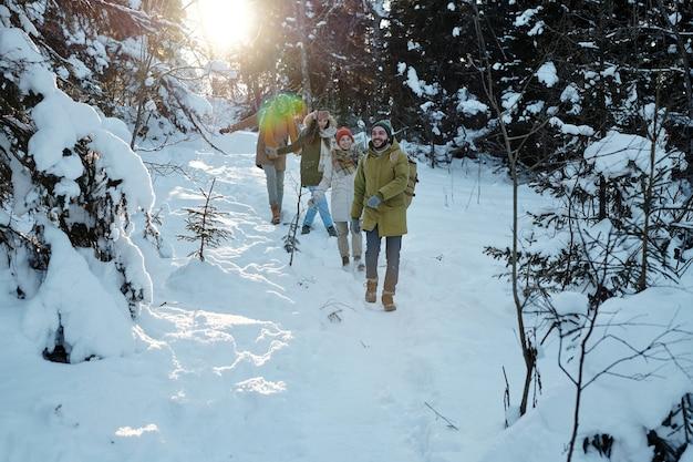 Gruppo di giovani amici felici che si divertono nella foresta invernale